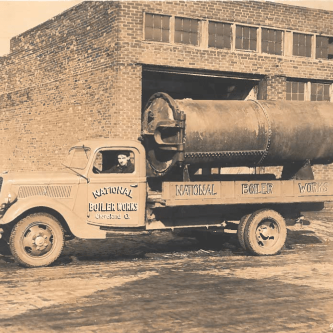 Old photo of National Boiler Works transporting a boiler.