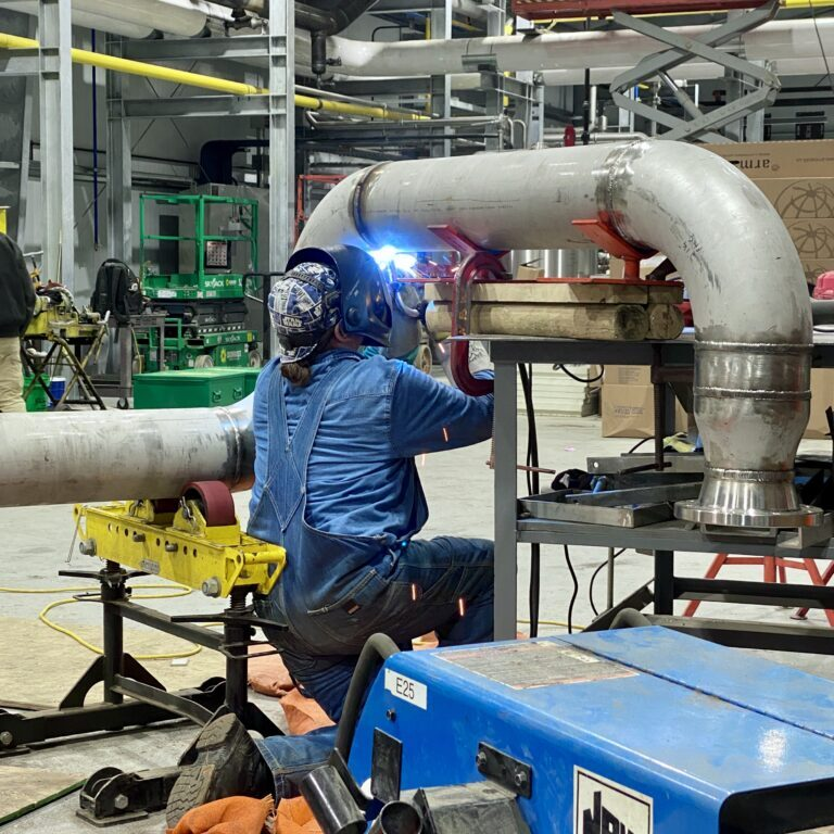 A worker welding a pipe. NBW Inc.