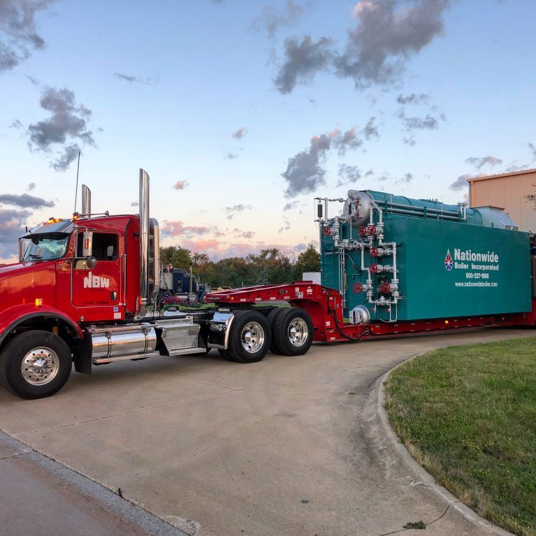 A red NBW truck driving a Nationwide Boiler. NBW Inc.